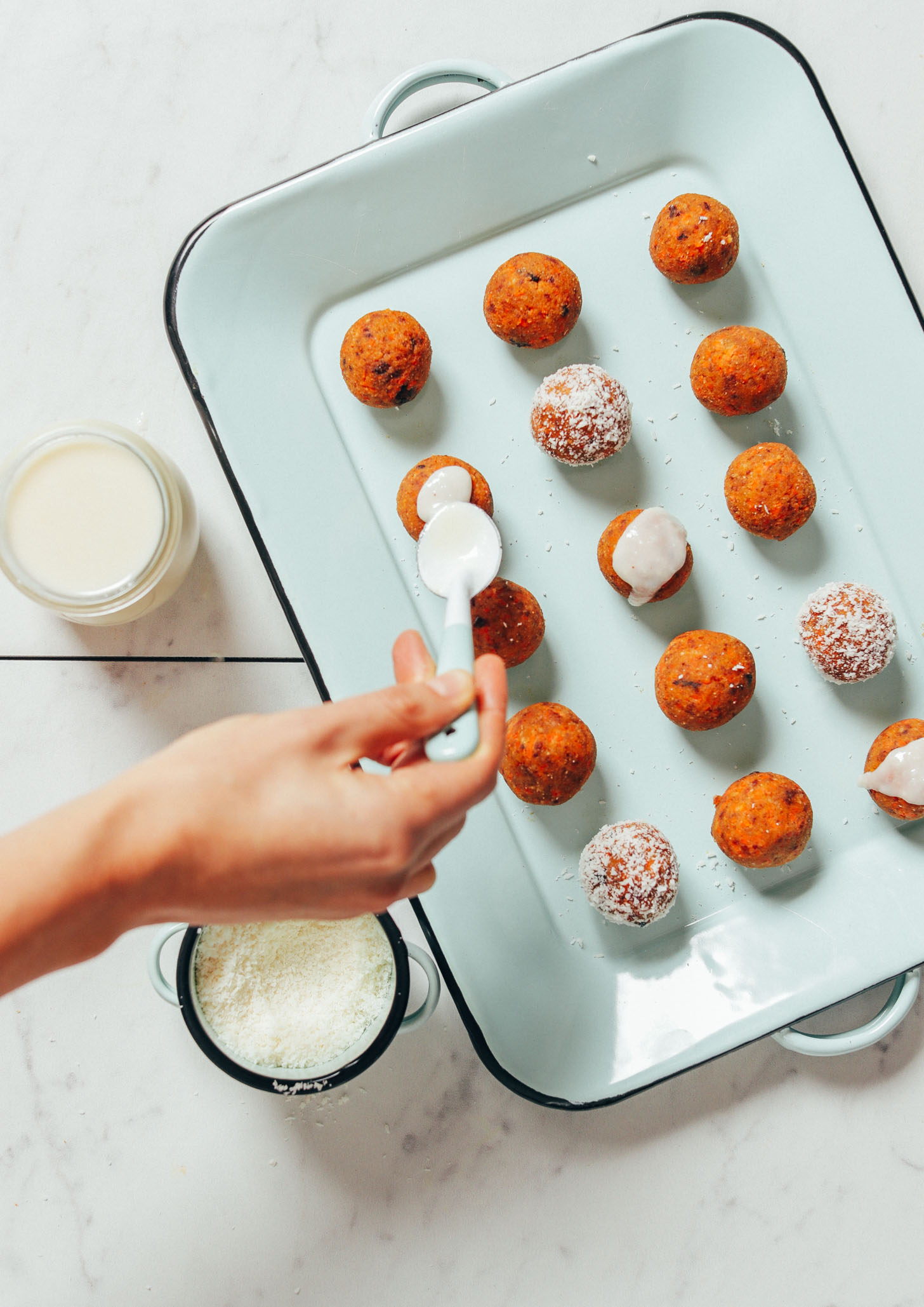 Using a spoon to spread coconut icing onto a Raw Carrot Cake Bite