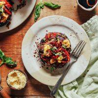 Plate with a grain-free Balsamic Portobello Pizza beside vegan parmesan, fresh basil, and balsamic reduction