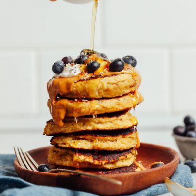 Drizzling syrup onto a stack of Banana Egg Pancakes topped with fresh blueberries and peanut butter