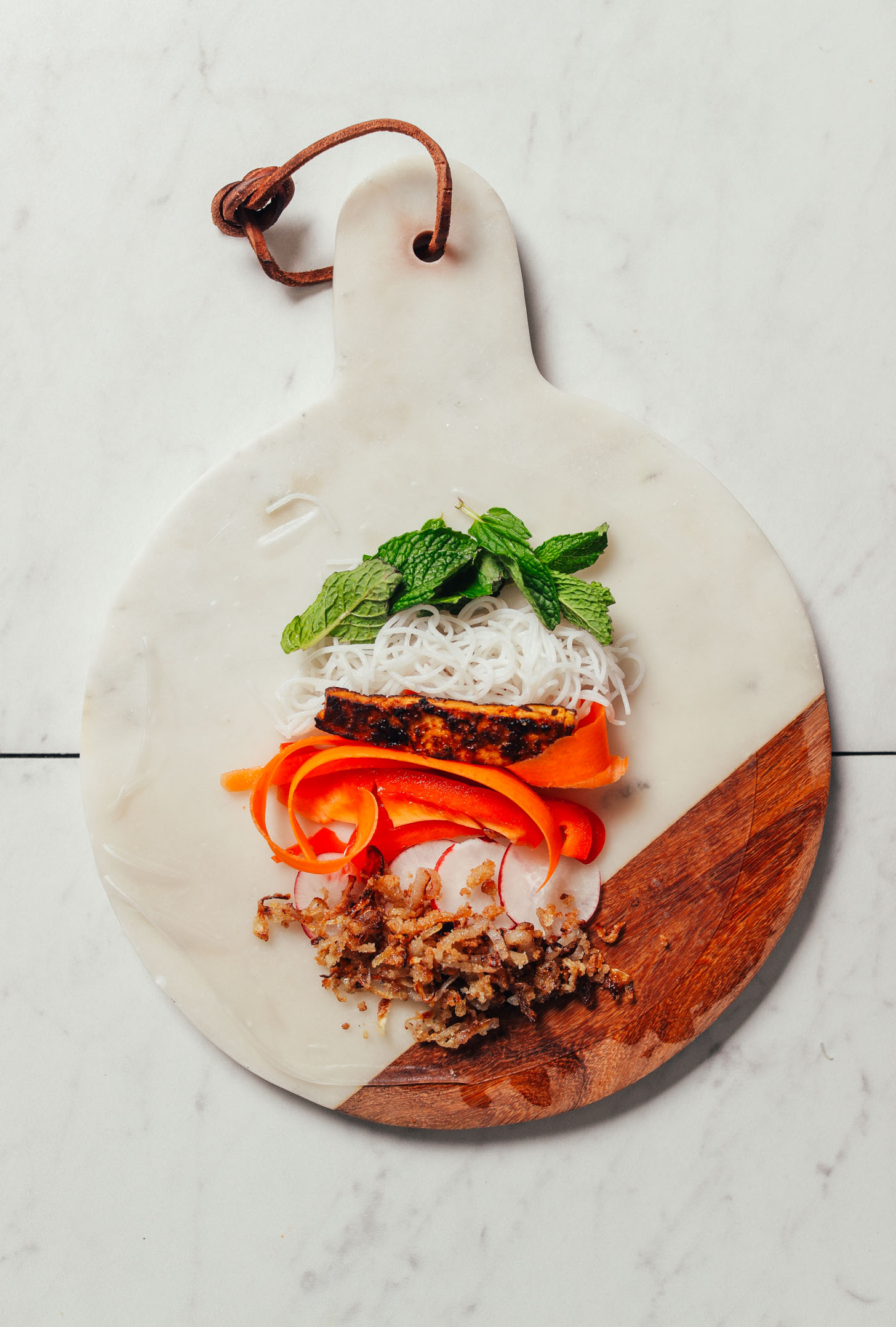 Marble and wood cutting board with a softened spring roll paper topped with fresh ingredients