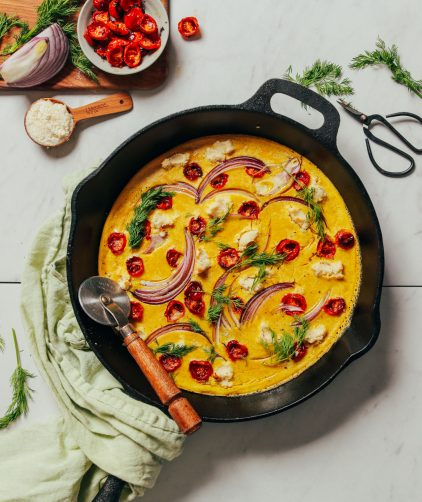 Skillet filled with our Vegan Frittata recipe made with red onion and cherry tomatoes