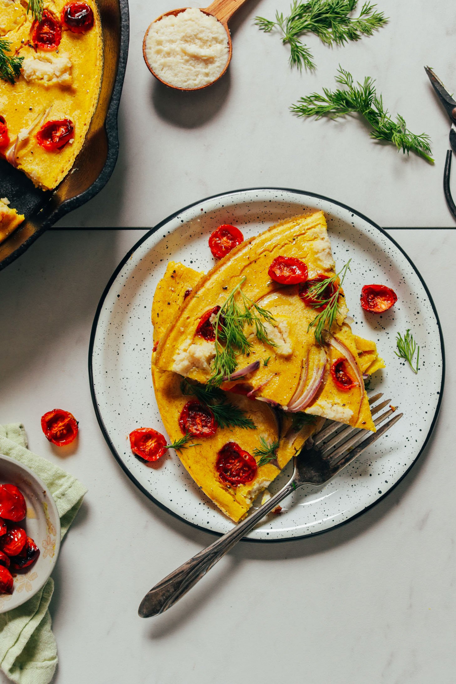 Plate with slices of Vegan Frittata topped with fresh dill and slow roasted tomatoes
