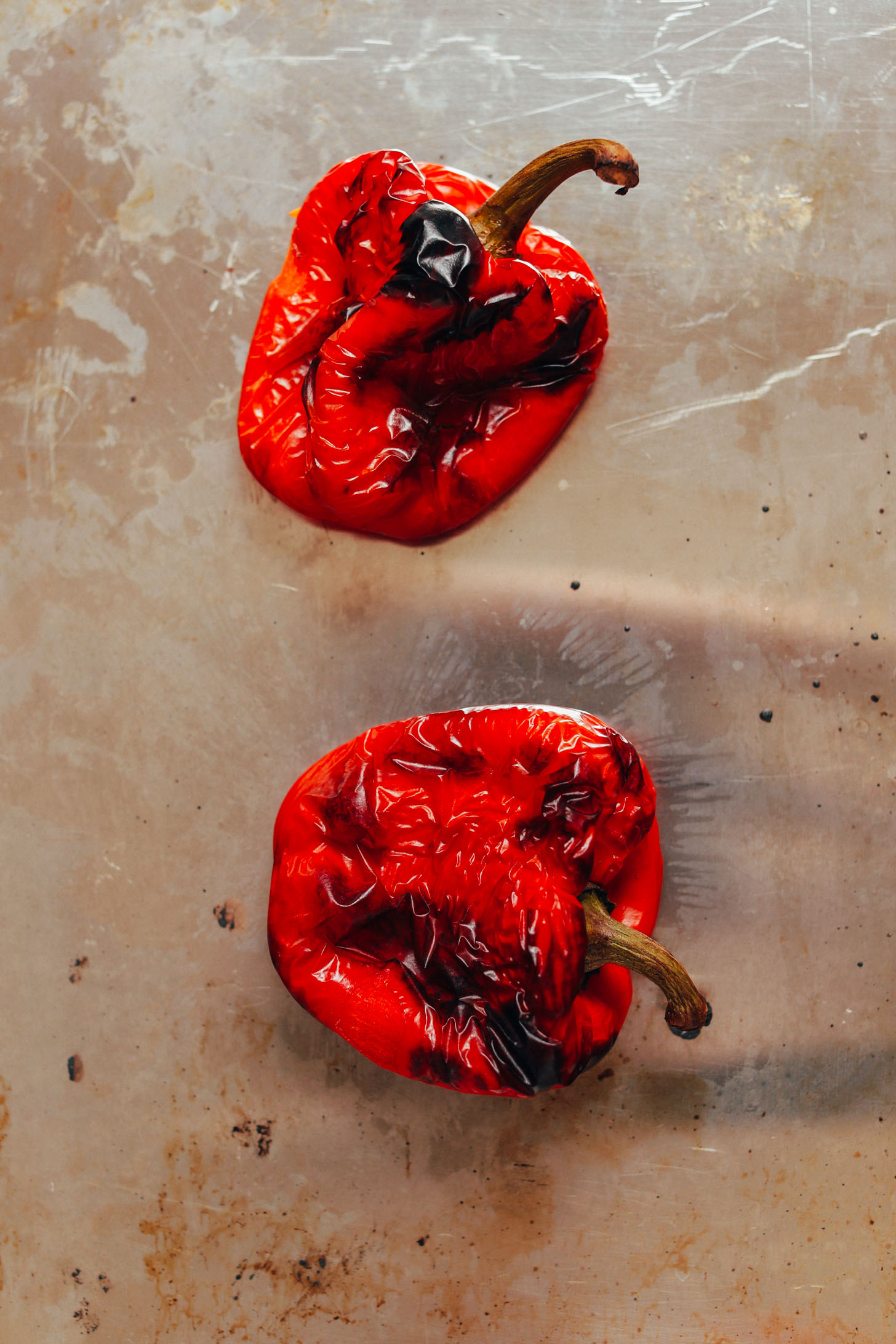 Baking sheet with two freshly roasted red bell peppers for making Romesco Sauce