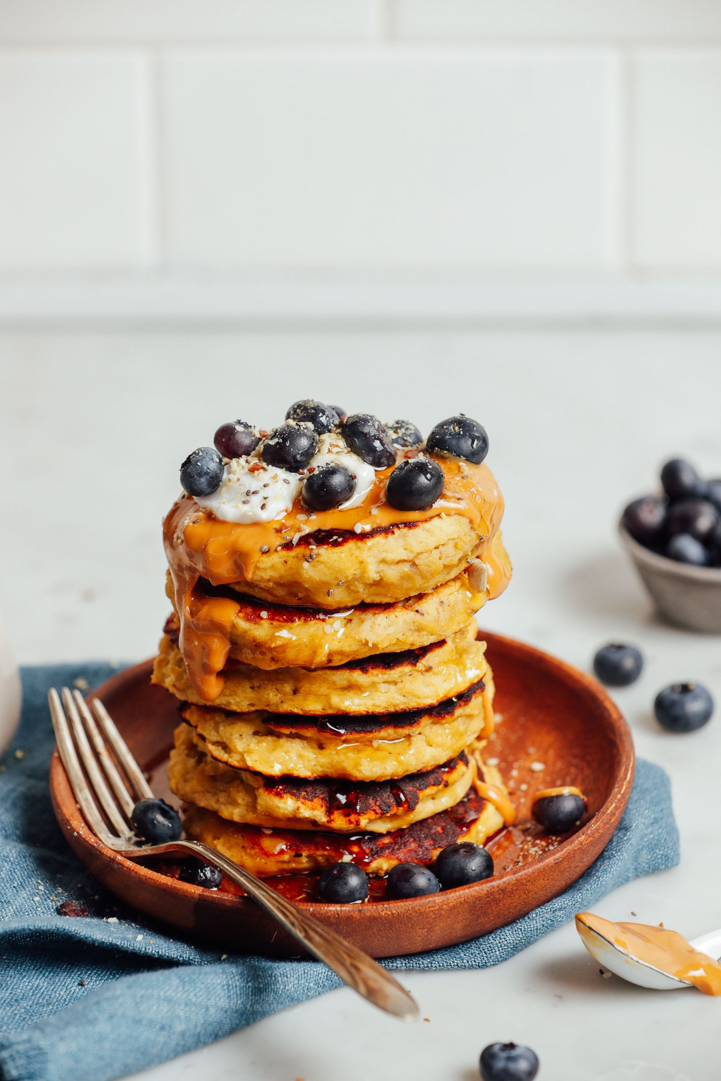 Stack of Banana Pancakes topped with peanut butter, coconut yogurt, and fresh blueberries
