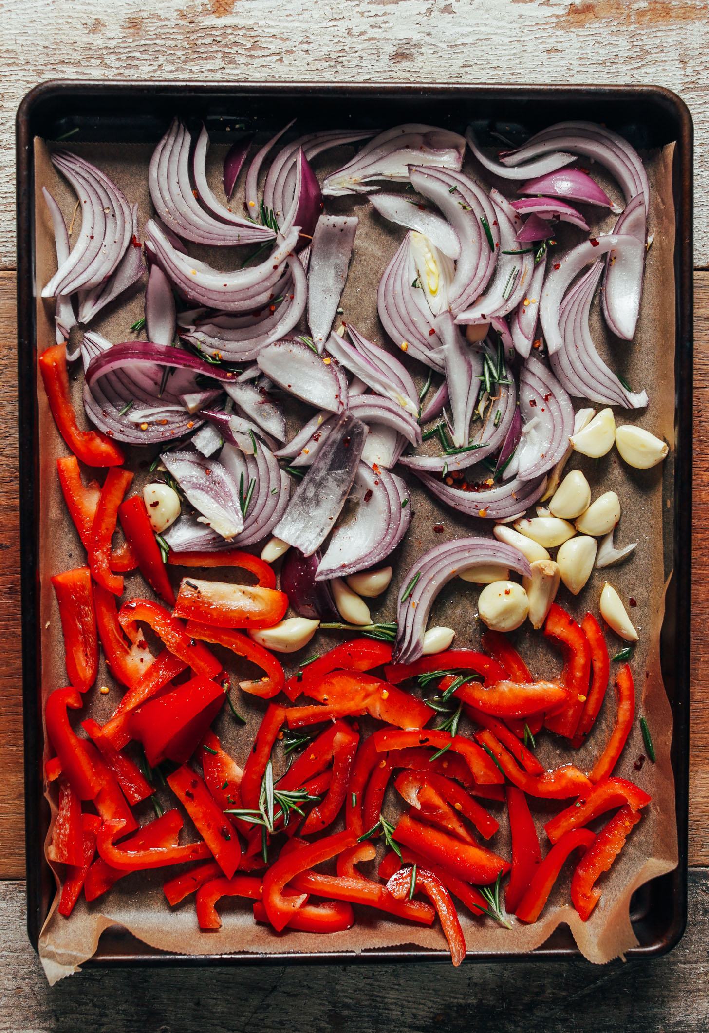 Parchment-lined baking sheet with peeled garlic, red onion, red bell pepper, and rosemary ready to be roasted