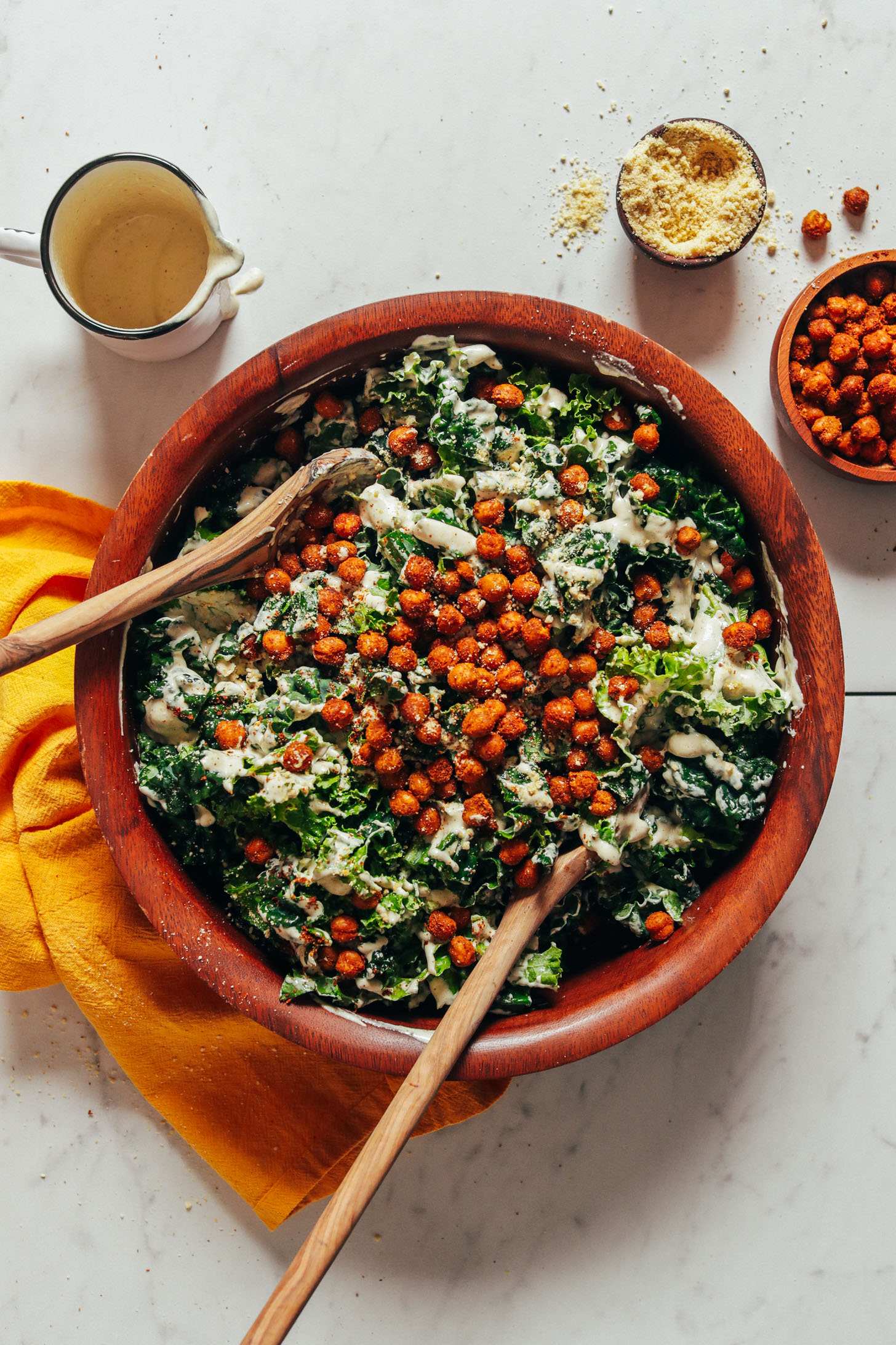 Wooden bowl of Chickpea Kale Caesar Salad topped with tandoori chickpeas