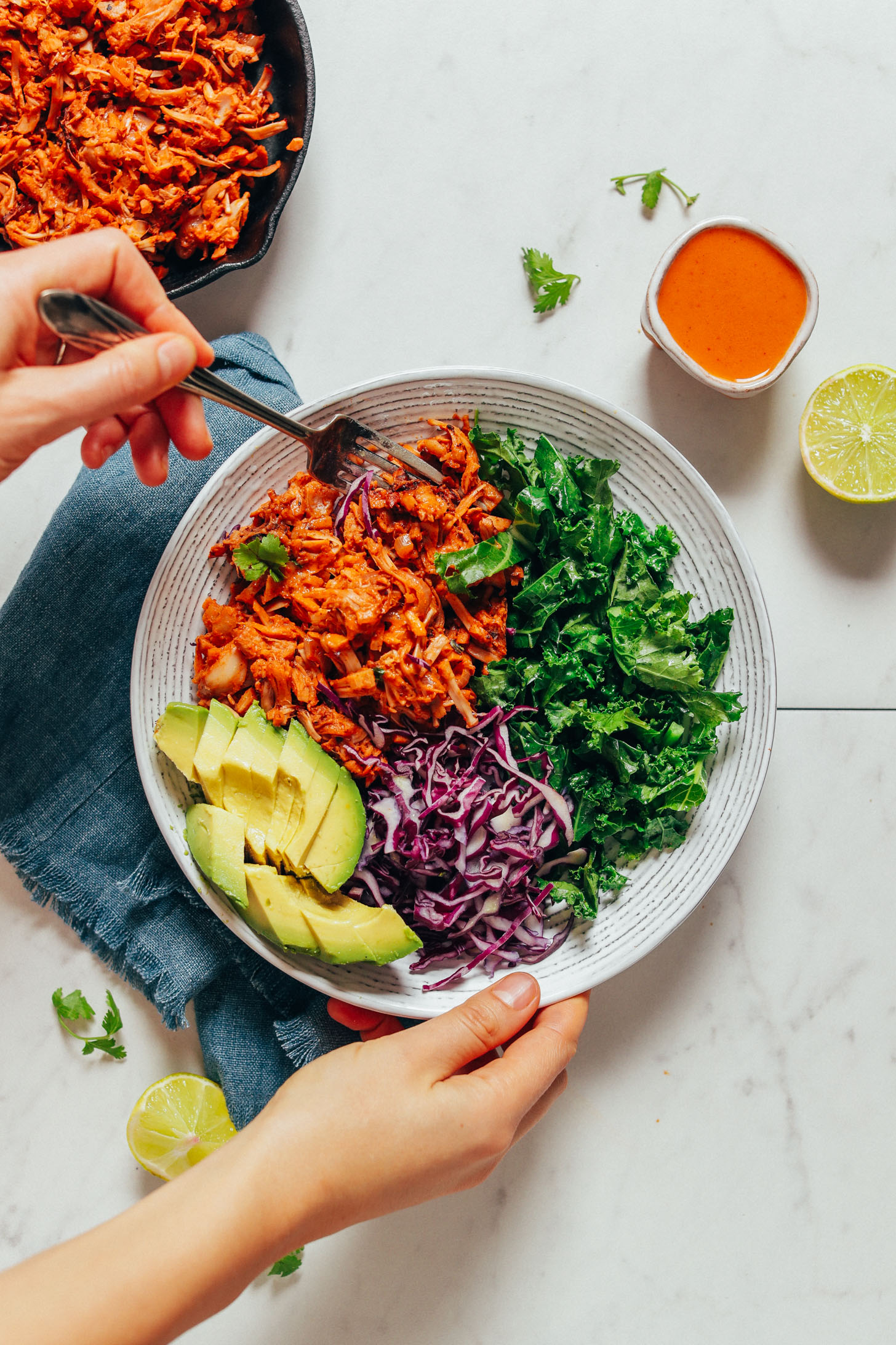 Using a fork to pick up a bite of Smoky Marinated Jackfruit from a bowl with fresh vegetables