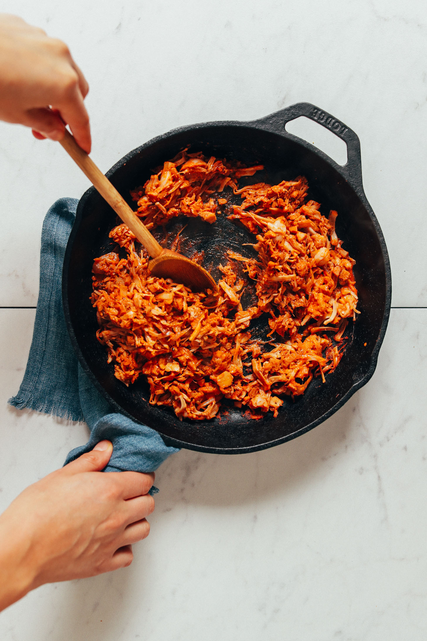 Using a wooden spoon to stir a skillet of Smoky Marinated Jackfruit