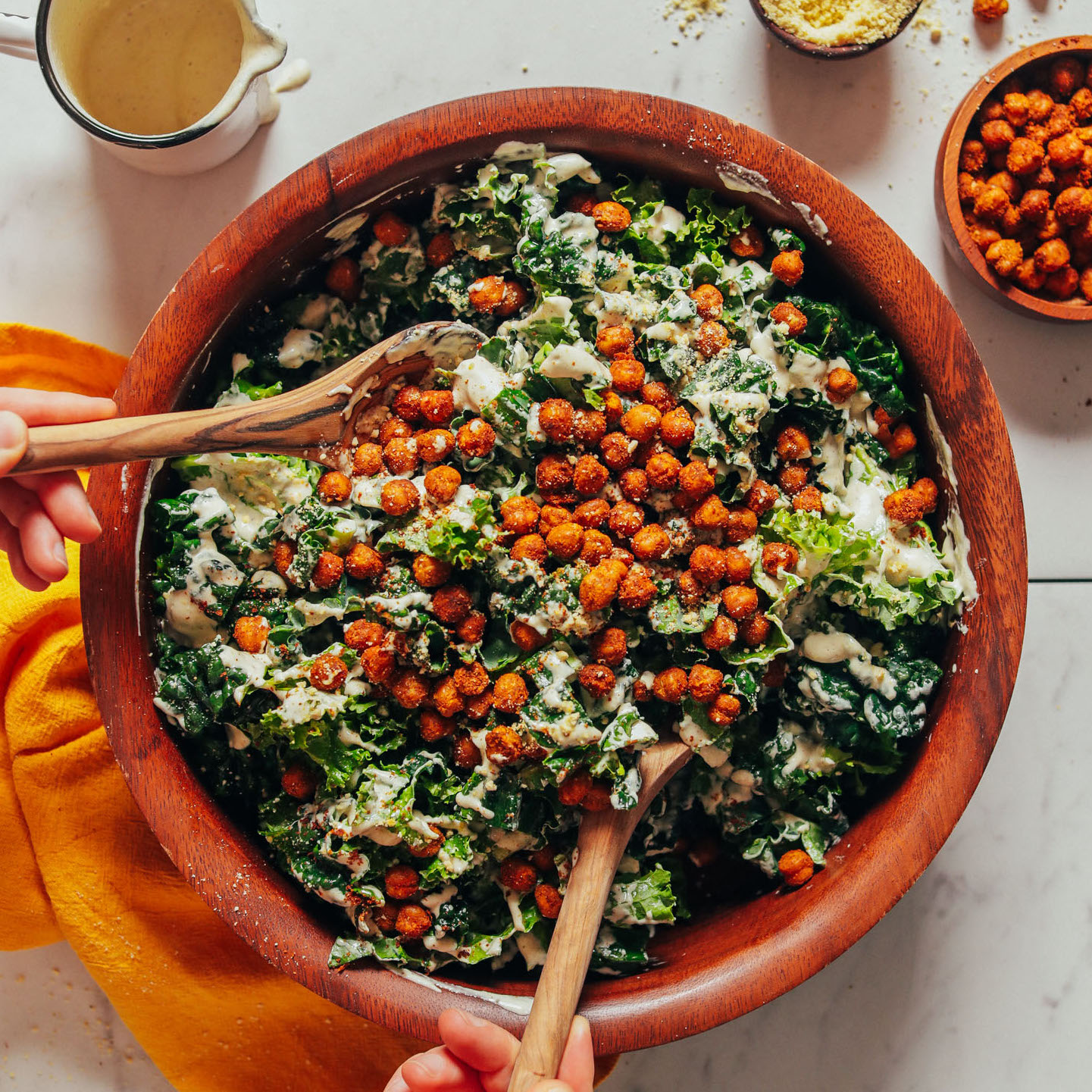 Using salad tongs to pick up a serving of our delicious Kale Caesar Salad with Crispy Chickpeas
