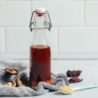 straight on shot of vegetarian fish sauce in a clear bottle with mushrooms on the side