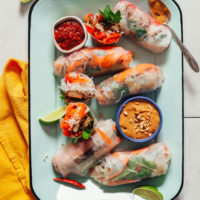 Tray of Crispy Shallot Spring Rolls with bowls of chili garlic and peanut sauces