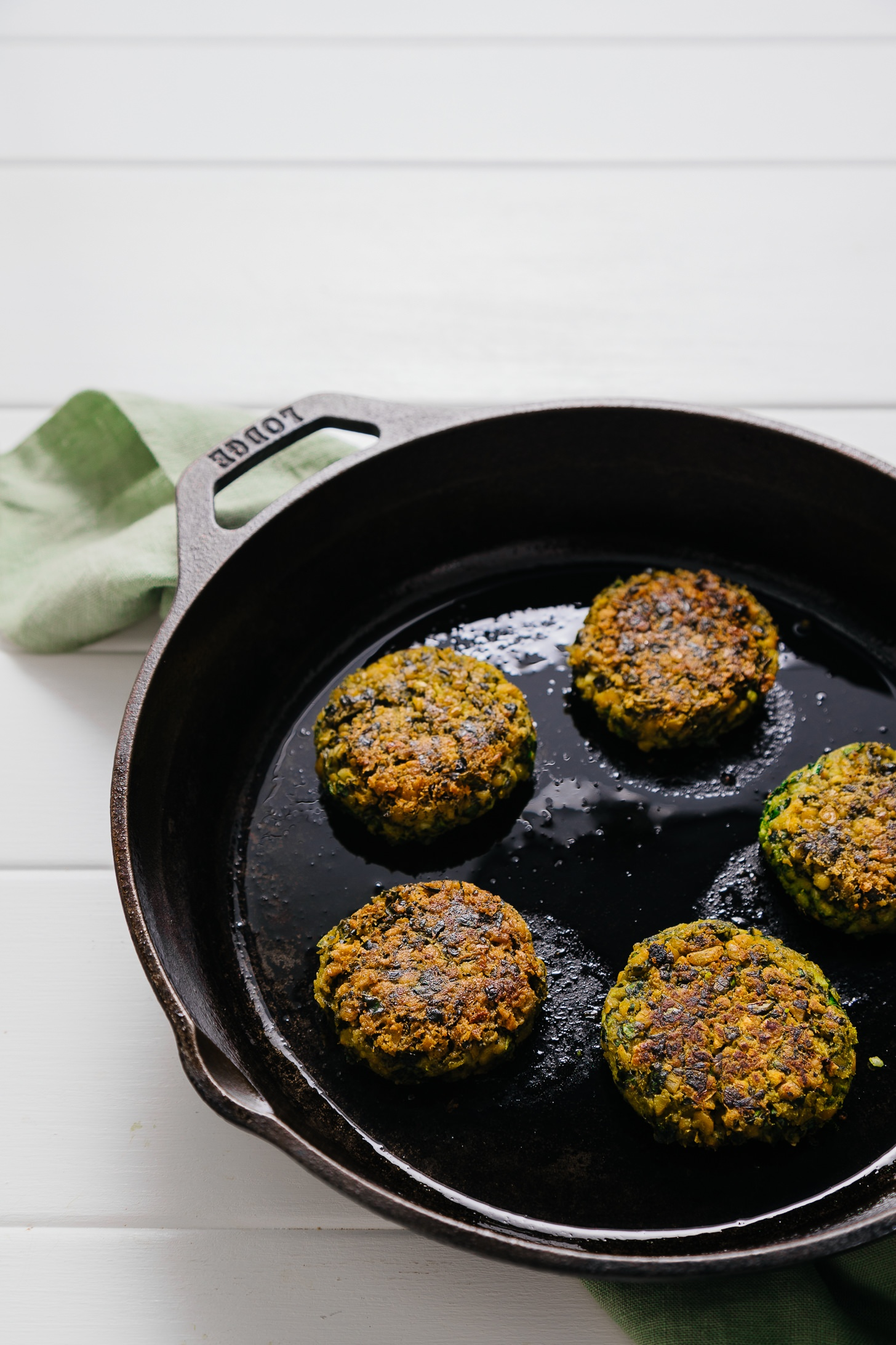 Healthy Kale Falafel cooking in a cast-iron skillet