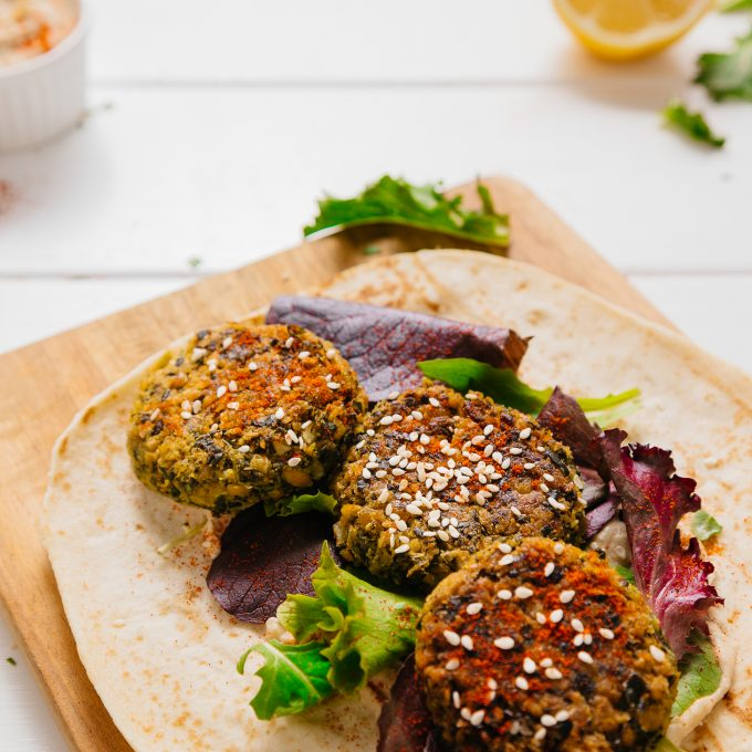 Kale Falafel Hummus Wrap on a wood cutting board