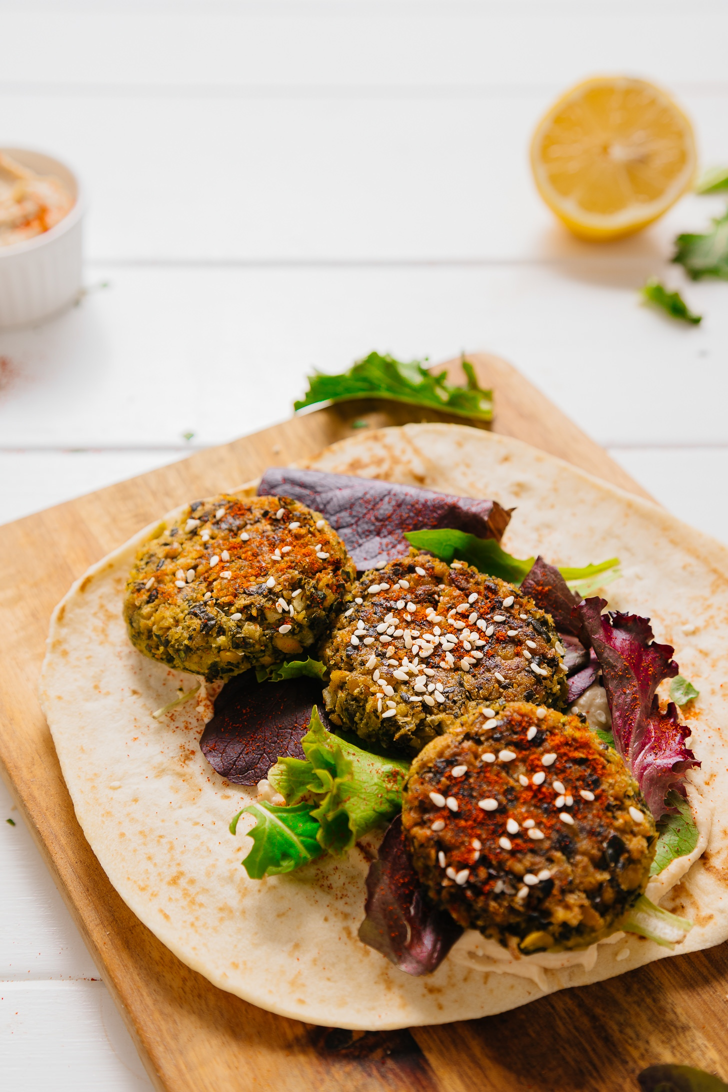 Cutting board with pita bread topped with greens and falafel made with kale