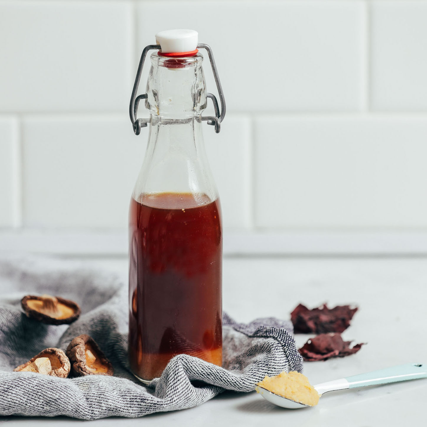Bottle of homemade Vegan Fish Sauce on a blue linen with ingredients used to make it