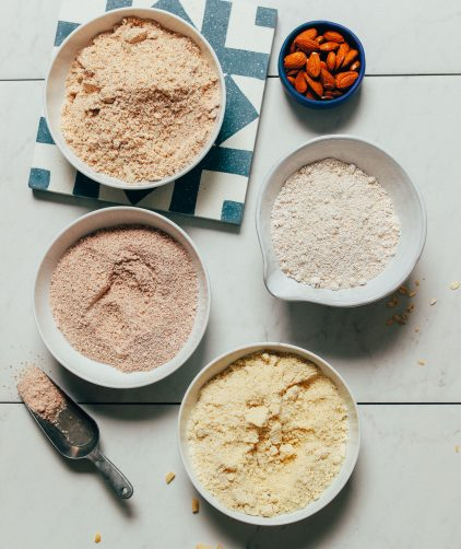 Bowls of oat flour, almond flour, almond meal, and almond pulp for our guide to how to use gluten-free flours