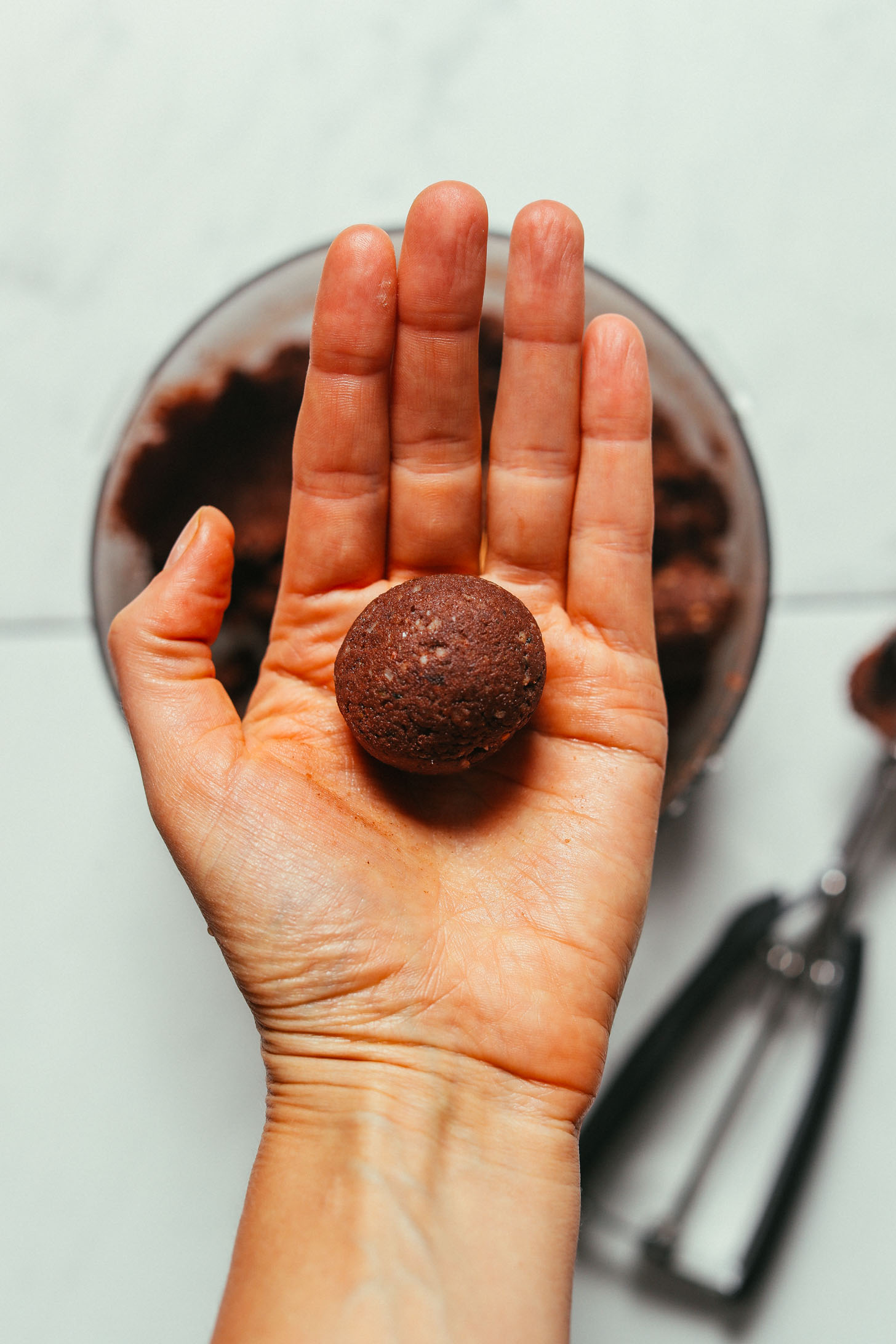 Holding up a Brownie Bliss Ball made with almond pulp and cacao powder