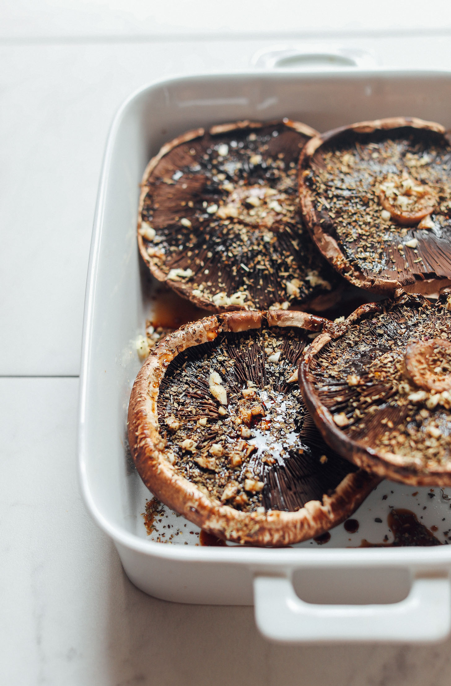 Baking pan filled with Balsamic Marinated Portobello Mushrooms topped with garlic and herbs