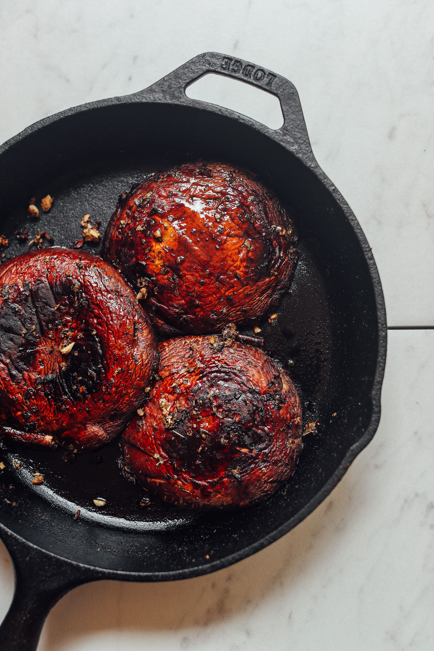 Cast-iron skillet of perfectly browned Balsamic Marinated Portobello Burgers