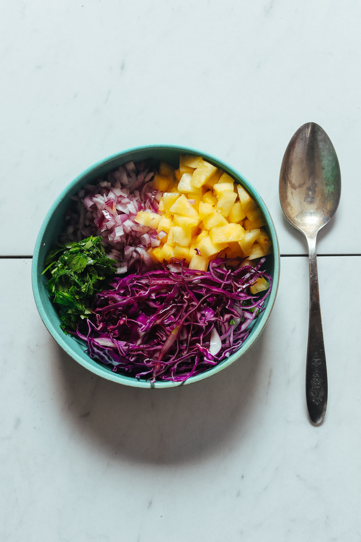 Bowl of diced pineapple, red onion, red cabbage, and cilantro ready to be stirred together for a Pineapple Cabbage Slaw