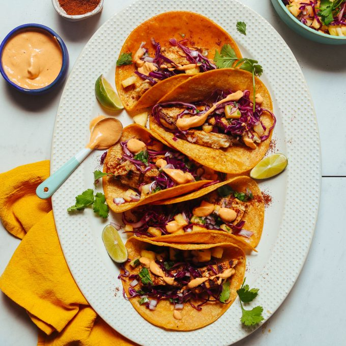 Large platter filled with dairy-free Grilled Fish Tacos topped with Pineapple Cabbage Slaw