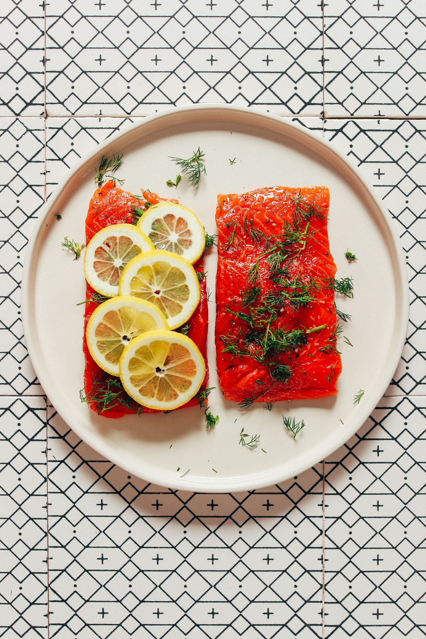Two filets of salmon; one topped with dill and the other with lemon slices and dill
