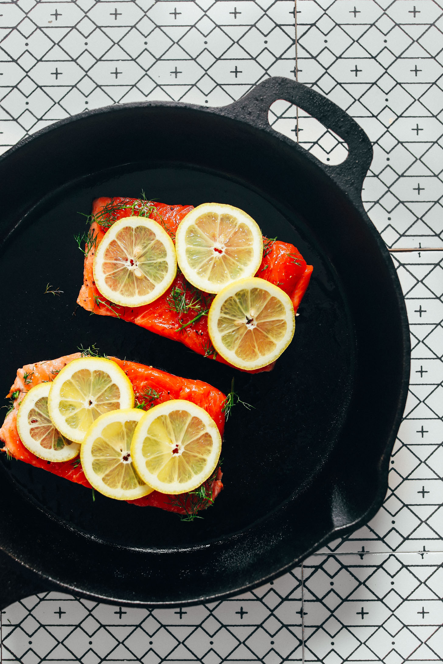 Cast-iron skillet with two filets of Lemon Baked Salmon with dill