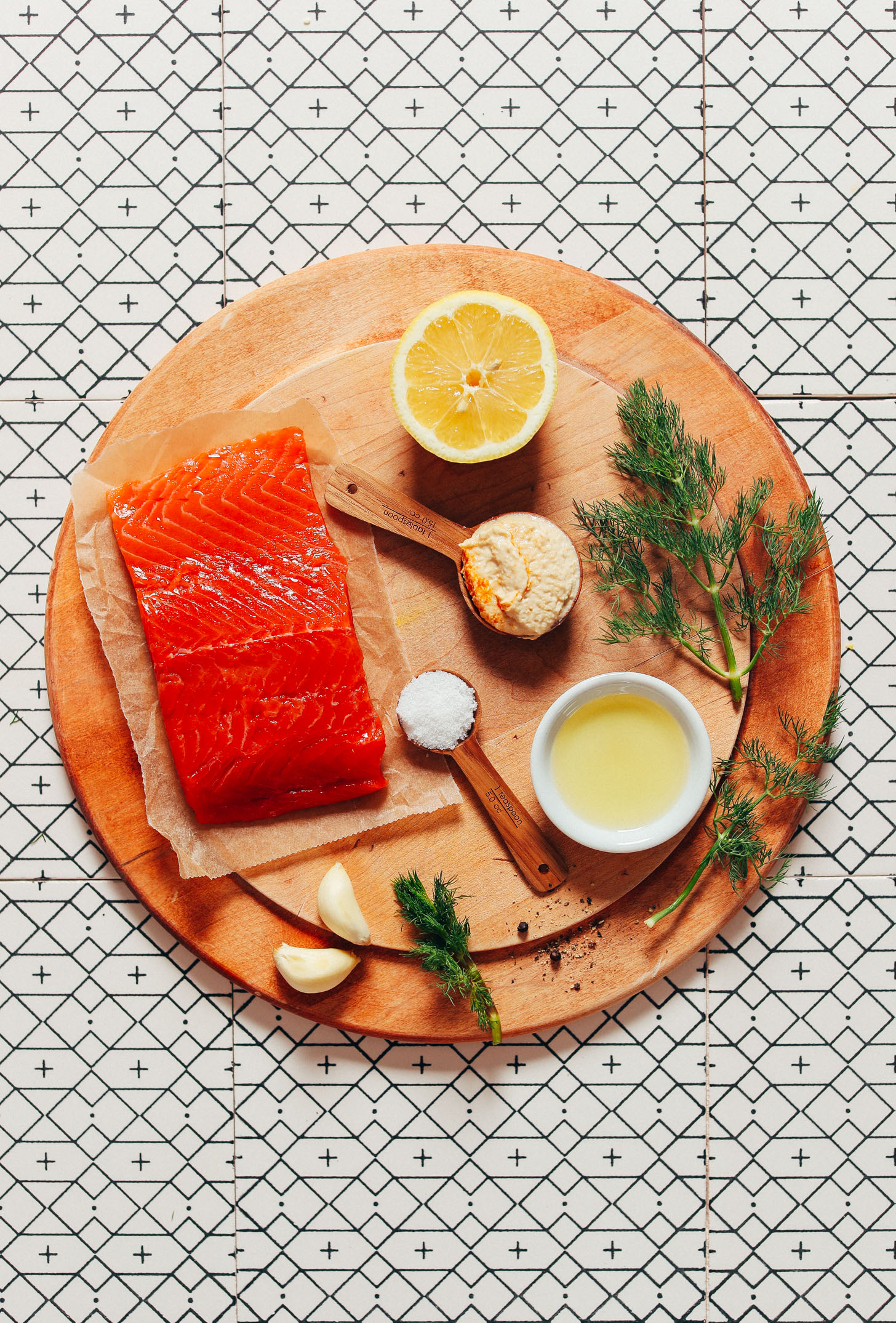 Wood cutting board with vibrant wild-caught salmon, garlic, dill, lemon, and other ingredients for making a delicious salmon recipe