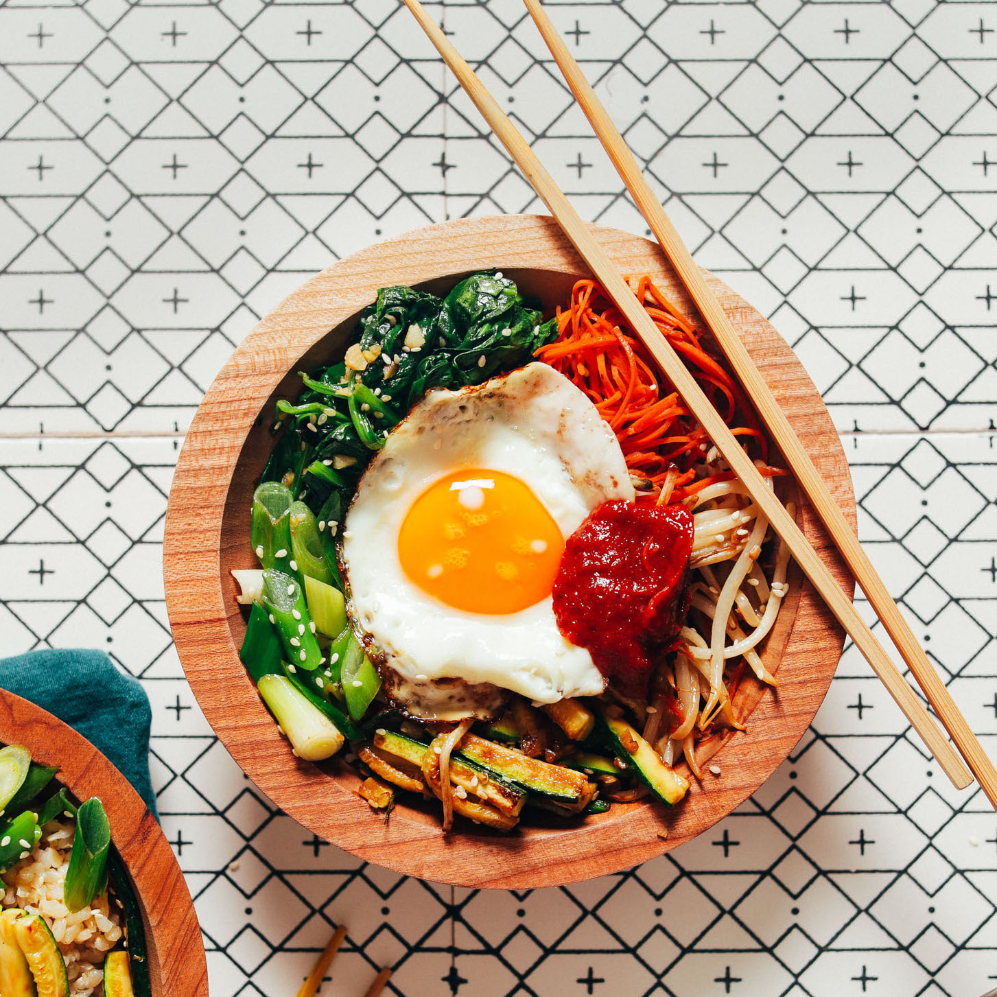 Chopsticks resting on a bowl of Bibimbap made with brown rice and lots of veggies