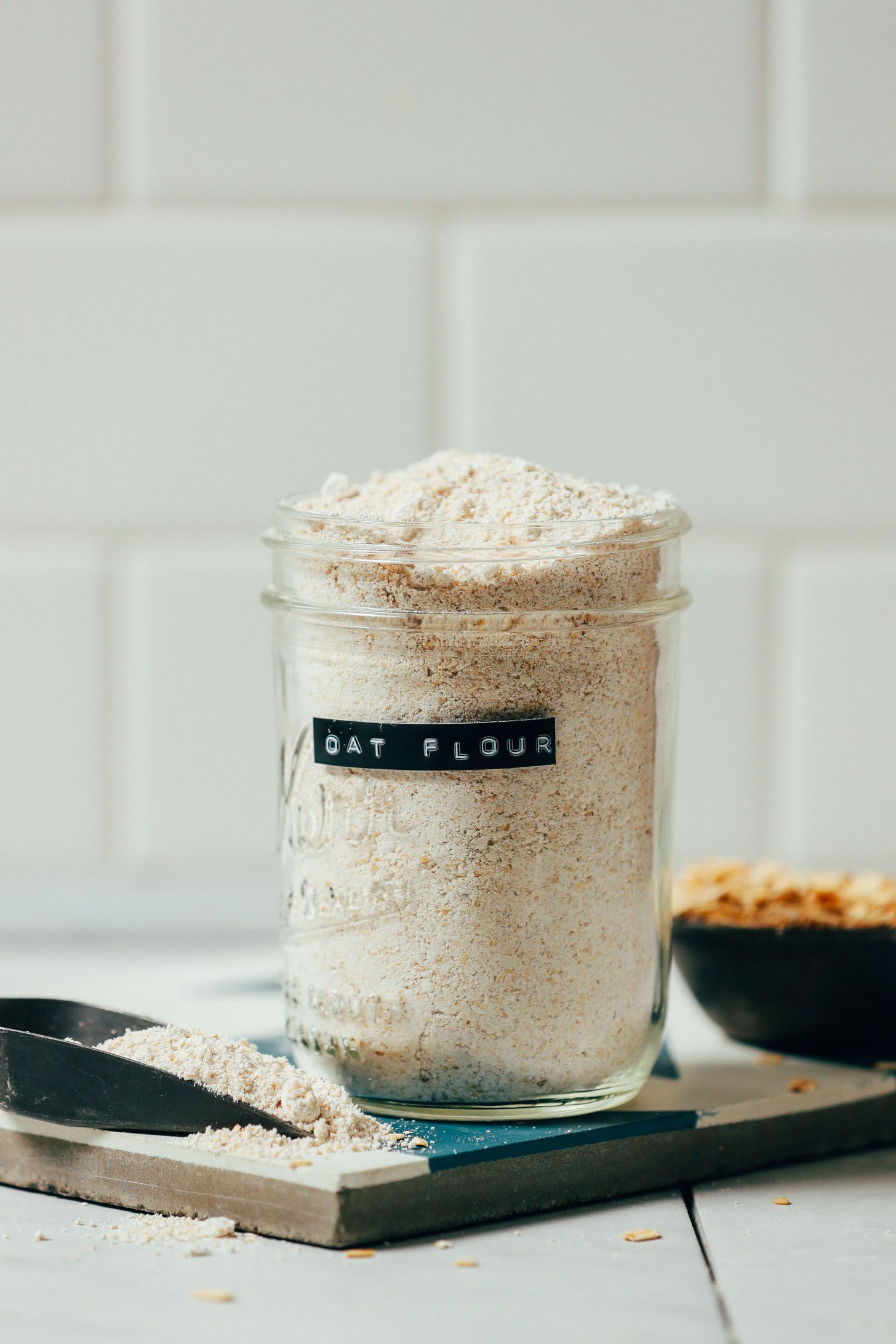 Scoop and jar of homemade oat flour made with our DIY Tutorial on How to Make Oat Flour