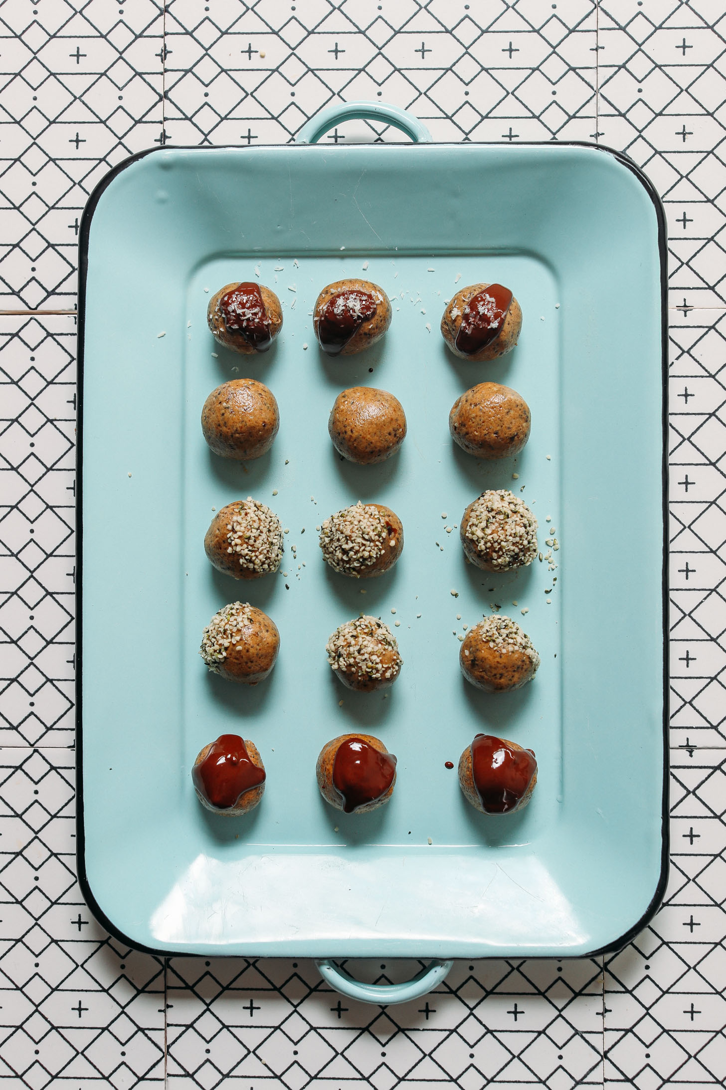 Blue tray filled with Protein Balls topped with melted chocolate and hemp seeds