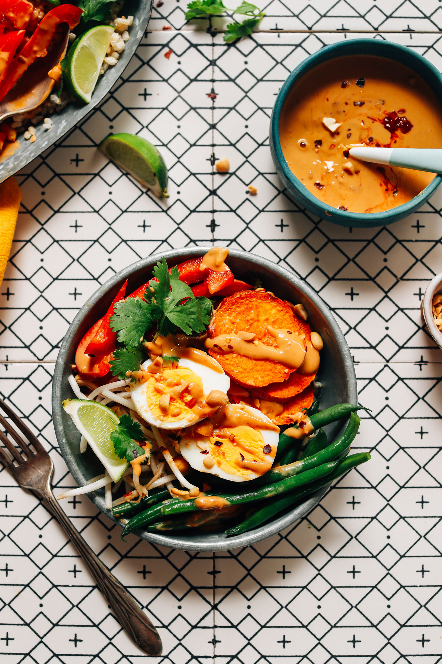Bowl of Gado Gado made with brown rice, green beans, sweet potato, bell pepper, egg, and Spicy Peanut Sauce