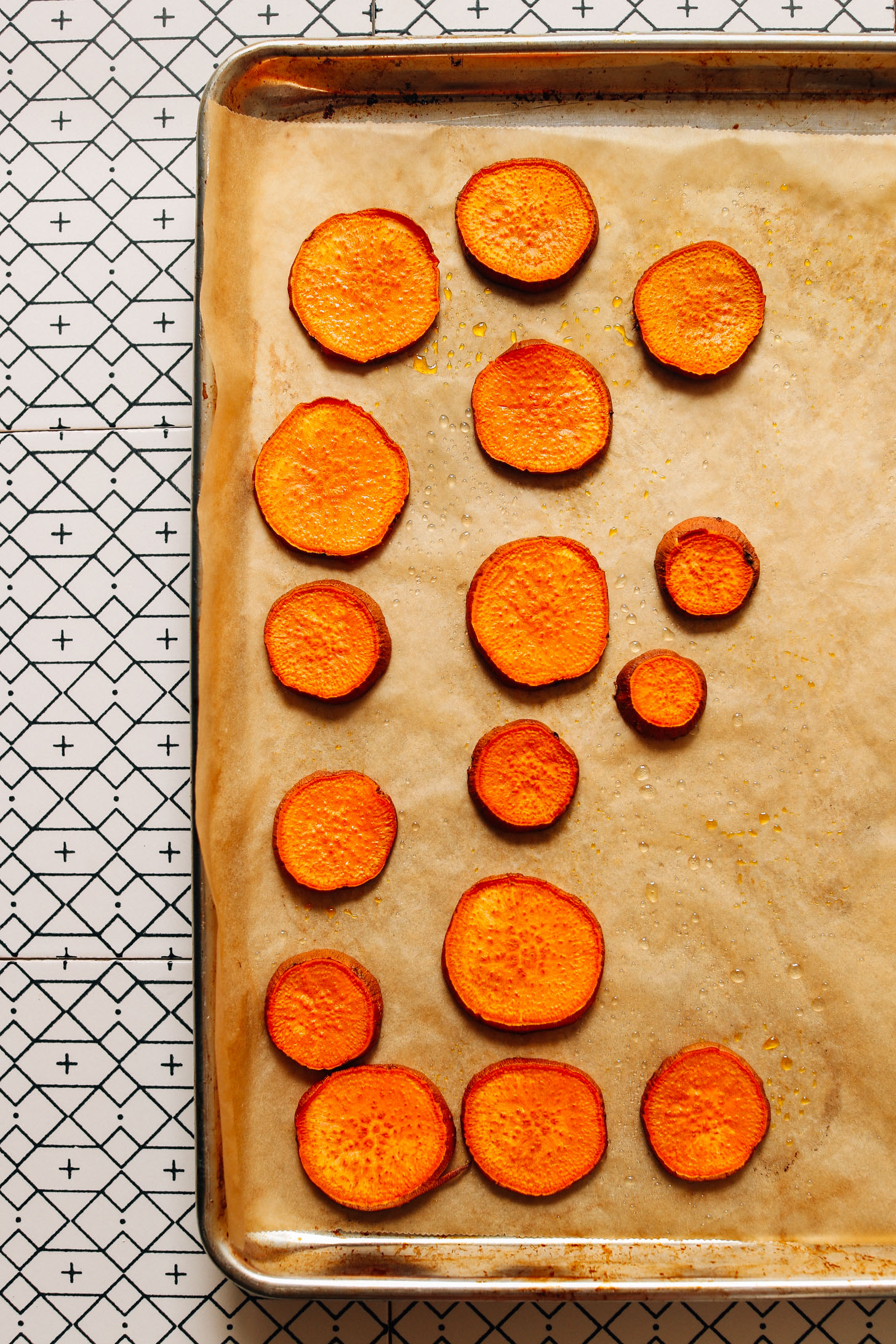 Parchment-lined baking sheet of freshly roasted sweet potato rounds for making Gado Gado
