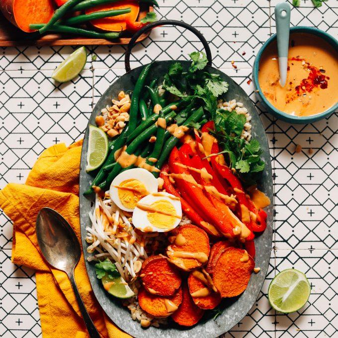 Tray of our delicious Gado Gado recipe beside a bowl of Spicy Peanut Sauce