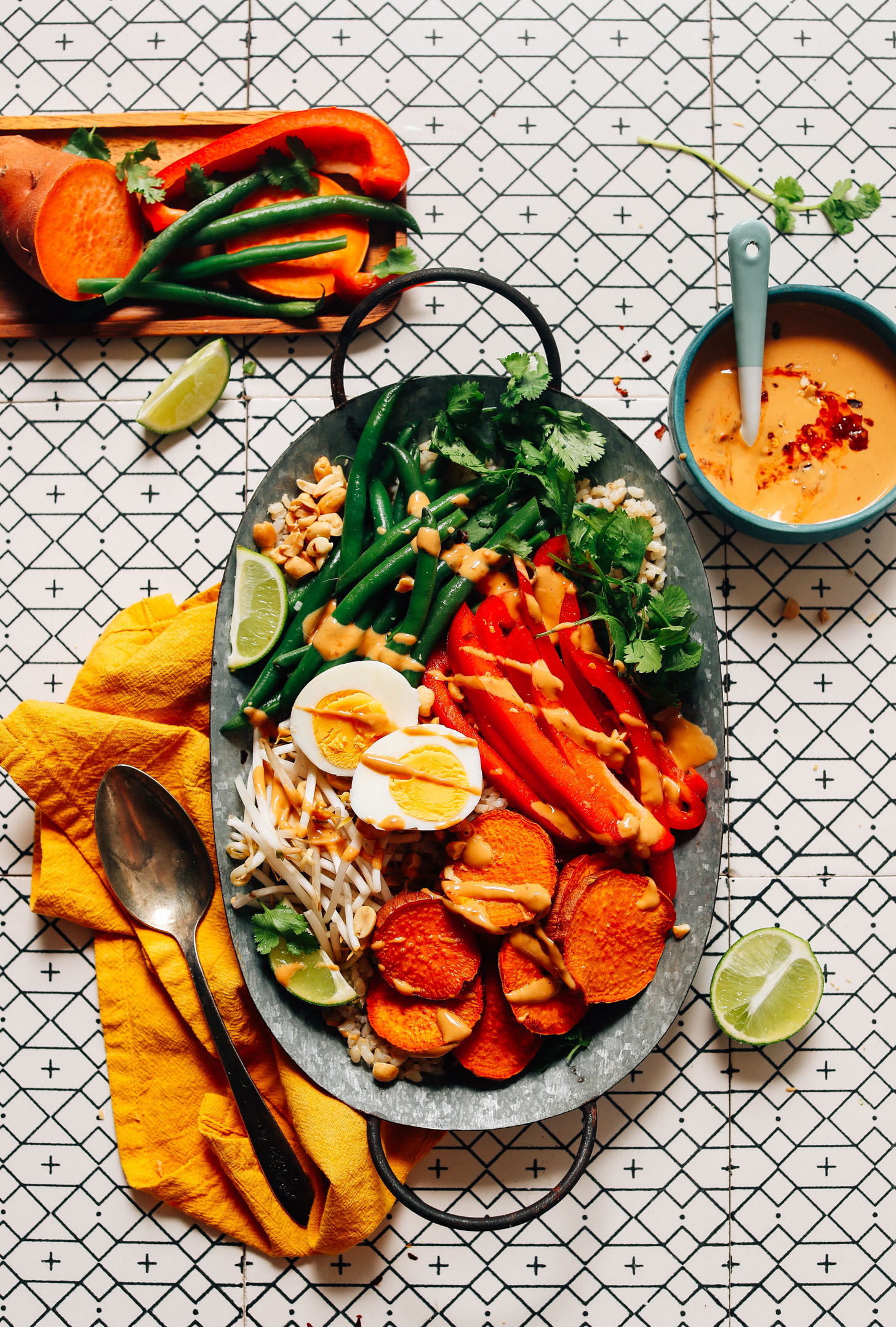 Tray of gluten-free Gado Gado made with brown rice, veggies, boiled egg, and a Spicy Peanut Sauce