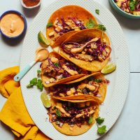 Spoonful of dairy-free chipotle aioli resting on a platter of Grilled Fish Tacos with Pineapple Cabbage Slaw