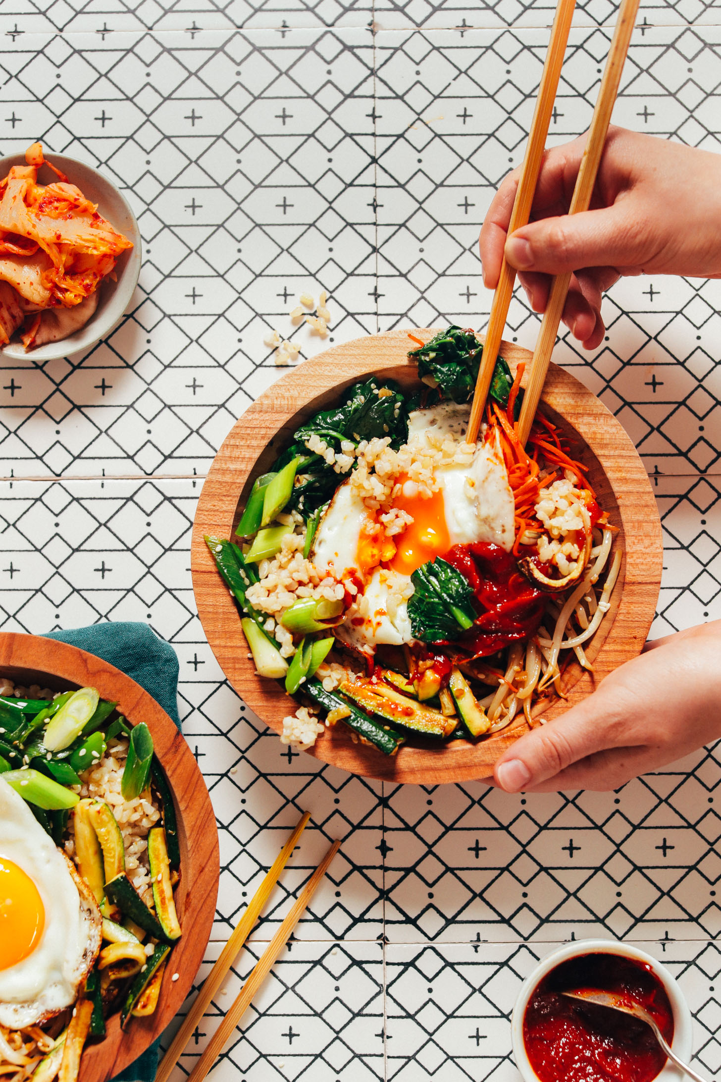 Using chopsticks to pick up a bite of a delicious homemade Korean Bibimbap bowl