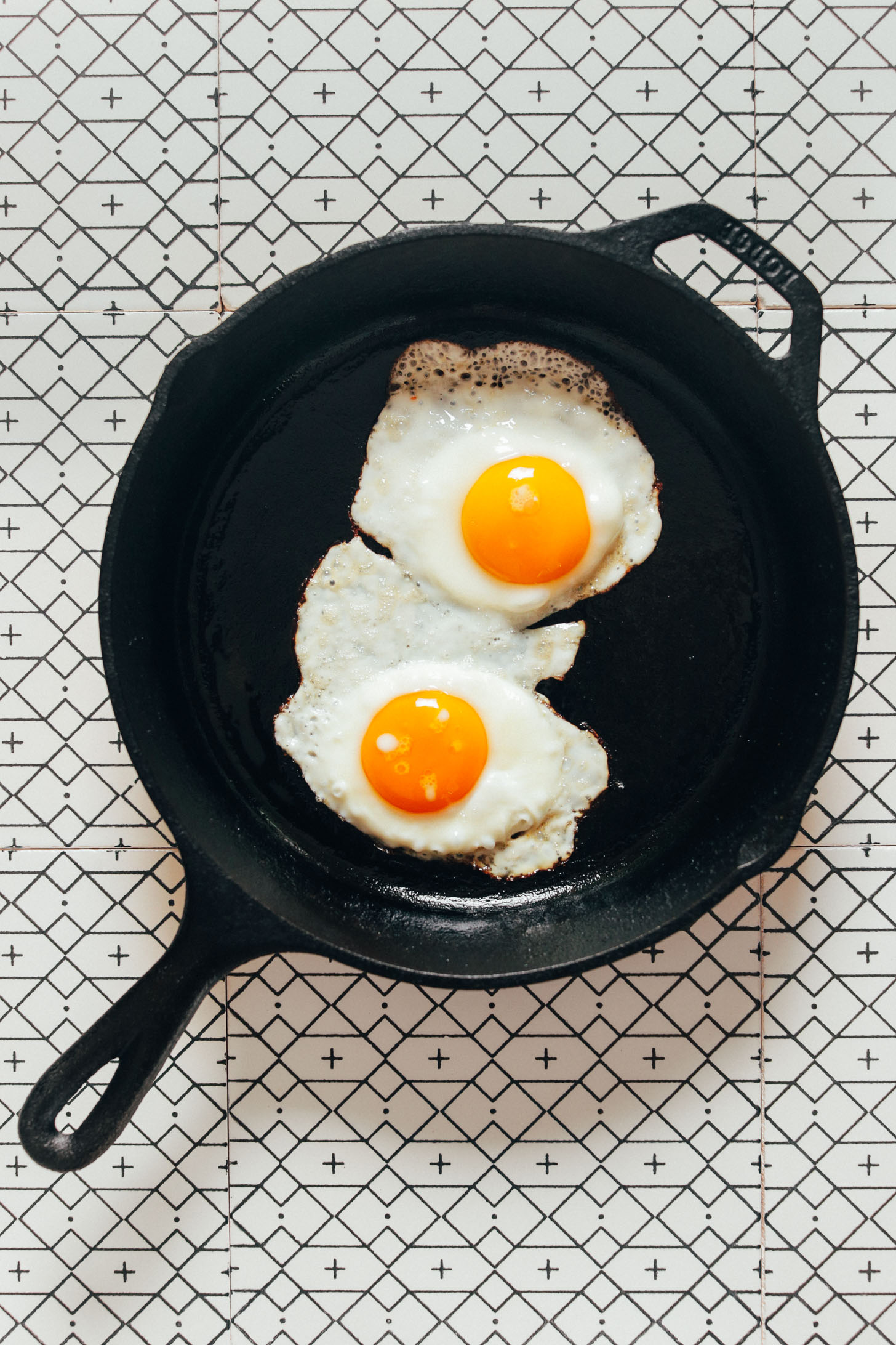 Two fried eggs in a cast-iron skillet for making Bibimbap