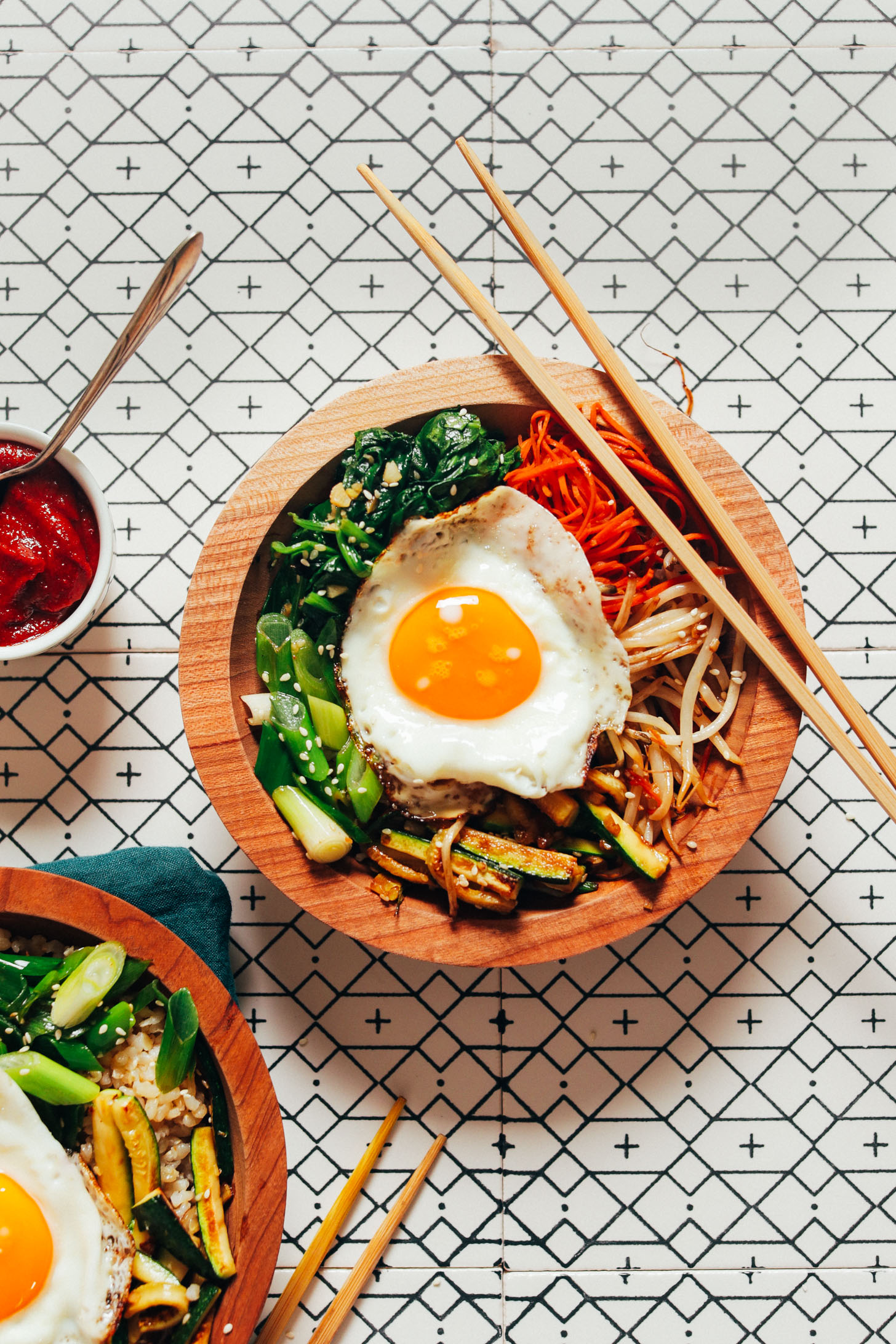 Chopsticks resting on and beside bowls of homemade Korean Bibimbap with fried eggs