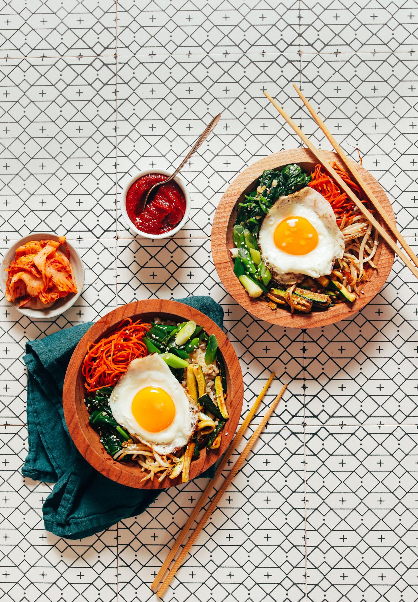 Bowls of homemade Korean Bibimbap with kimchi and Gochujang sauce