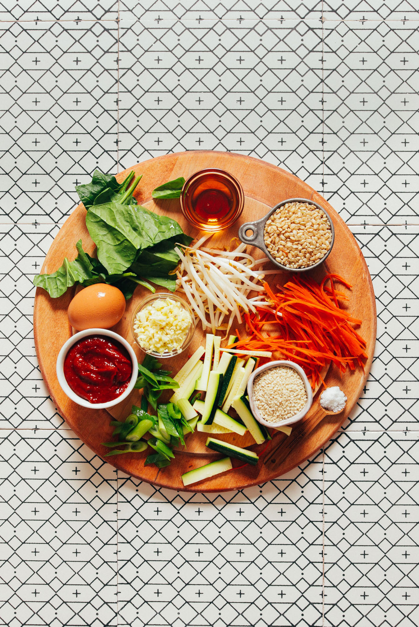 Wood cutting board with brown rice, vegetables, and an egg ready to show How to Make Korean Bibimbap