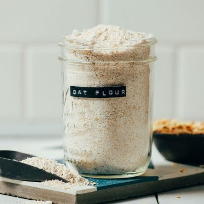 Jar and scoop of homemade oat flour sitting beside a bowl of oats