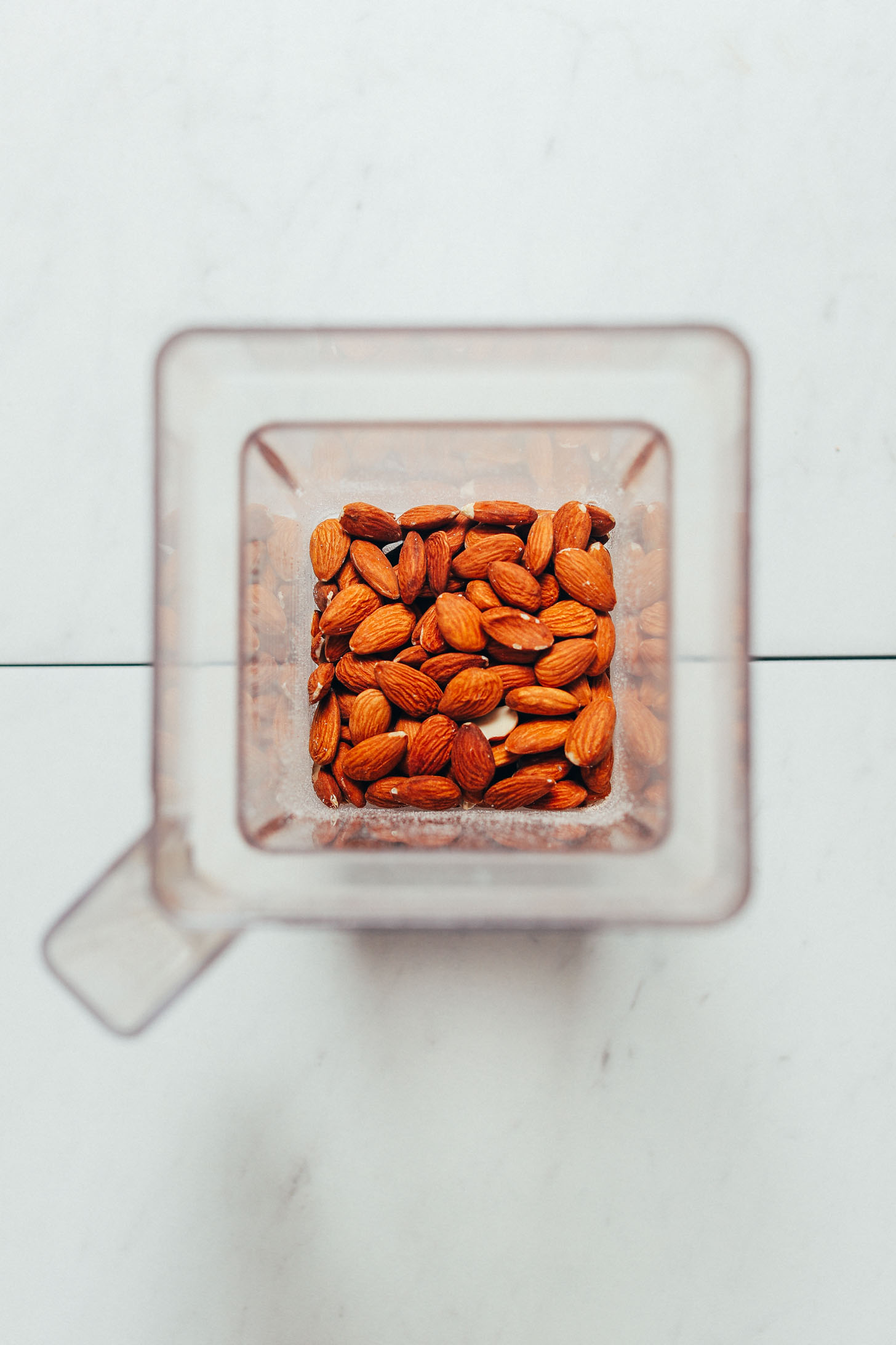 Blender filled with raw whole almonds for making almond meal