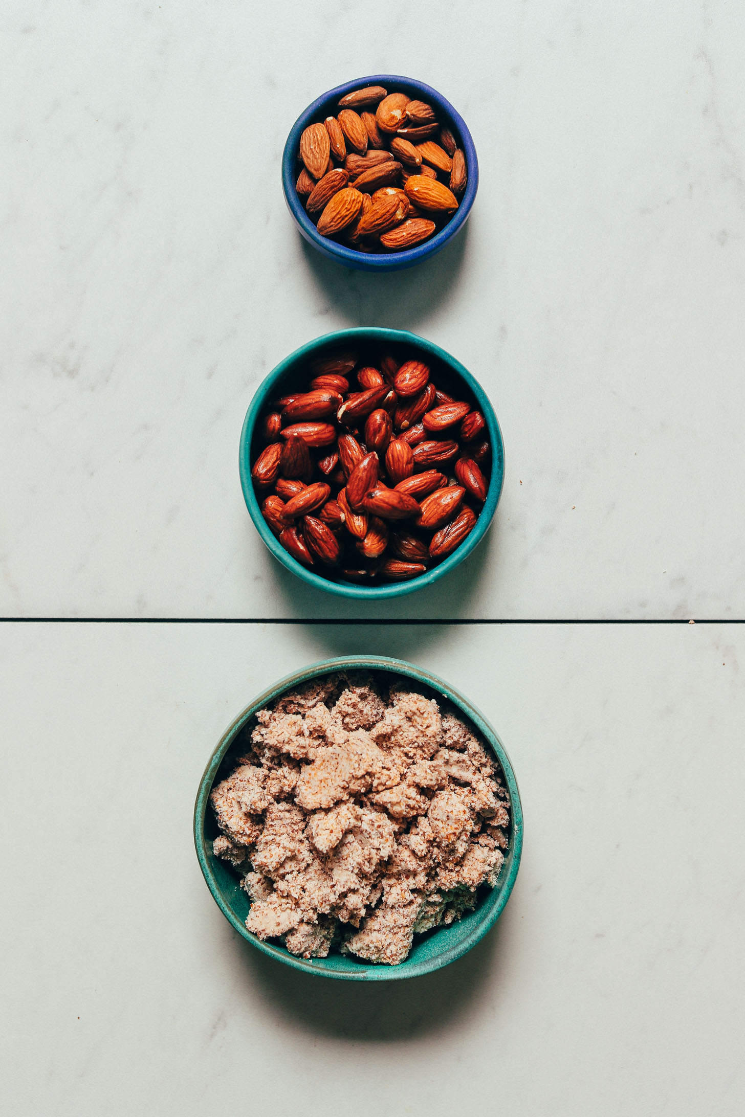 Bowls of raw almonds, soaked almonds, and almond pulp for our tutorial on How to Make Almond Meal from Almond Pulp