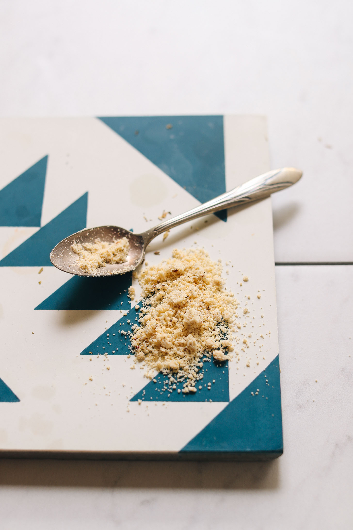 Spoonful of yeast-free Vegan Cashew Parmesan on a blue and white tile
