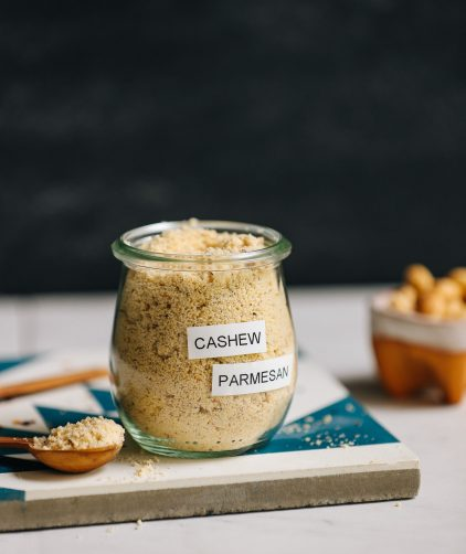 Plate with a glass jar of Vegan Cashew Parmesan made with yeast