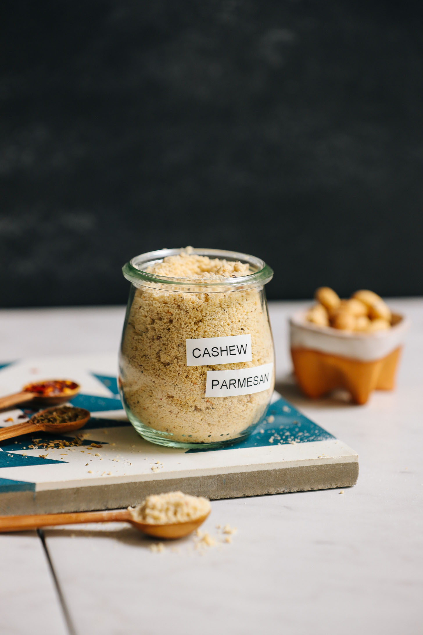 Jar of yeast-free, dairy-free, homemade Parmesan cheese beside ingredients used to make it