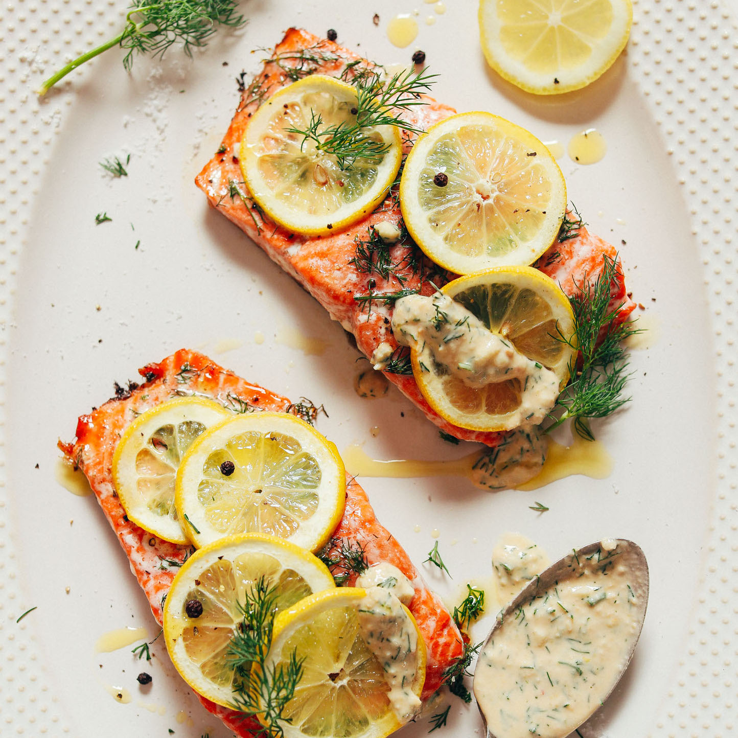 Close up shot of two filets of freshly baked salmon topped with dill, lemon, and garlic sauce