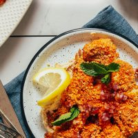 Plate of our Cashew-Crusted Cauliflower Steak recipe with the title overlaid in text