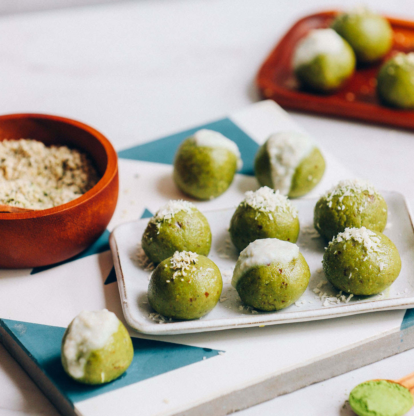 Tray of low sugar, date-sweetened Matcha Bliss Balls beside a bowl of hemp seeds